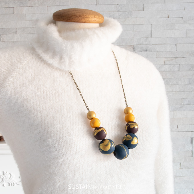 Necklace with painted wood beads on gold chain placed over mannequin with a white sweater.