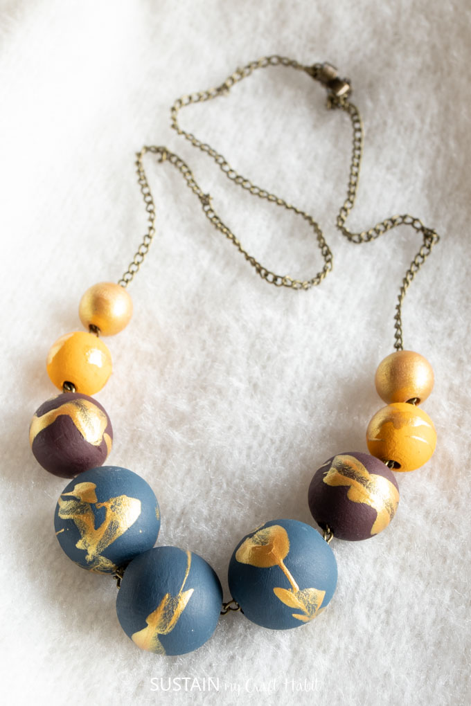 Close up of completed and painted wood bead necklace DIY jewelry idea.