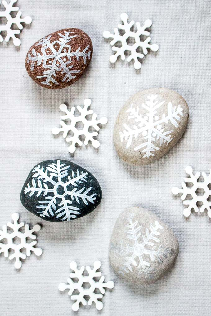 Four rocks painted with snowflake designs alongside snowflake decorations.