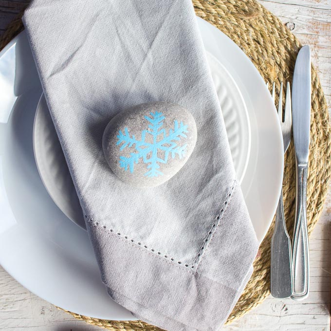 Painted snowflake rock being used as a napkin weight.
