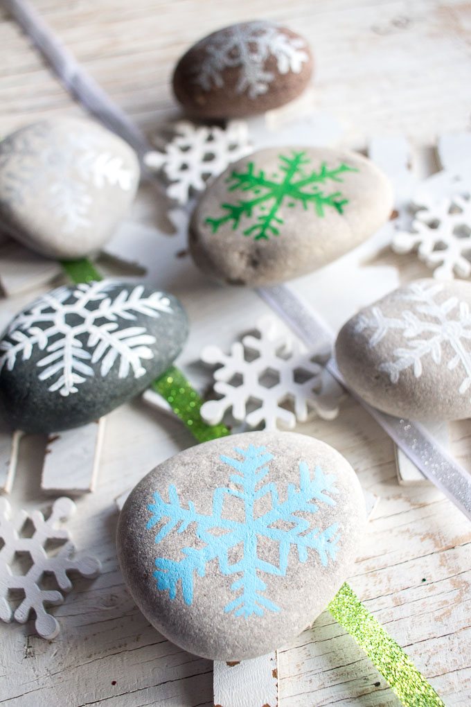 Six rocks painted with snow flake designs. They're placed on top of snowflake decorations and a white table.