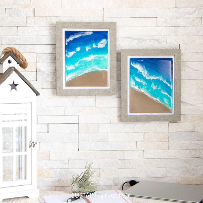 Two framed beach resin artwork pieces hung on a wall above an office desk.