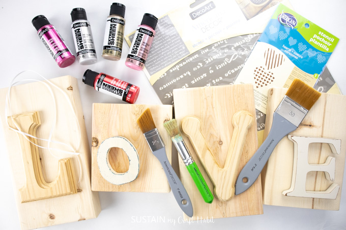 Craft materials that include wooden blocks with letters l,o,v,e, paint brushes, stencils and paint