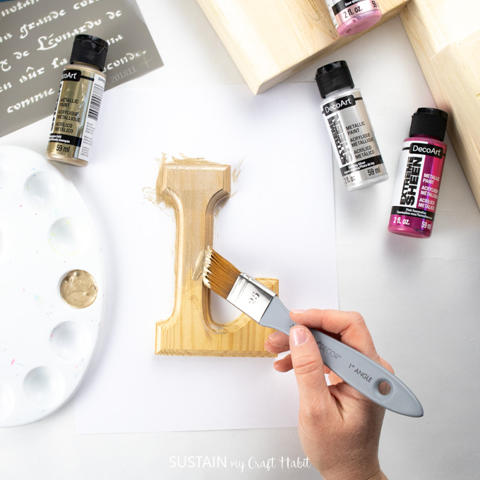 painting the letter L with gold paint.