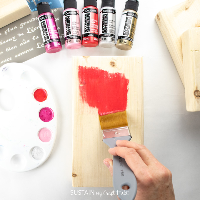 Painting a wood block with red paint.