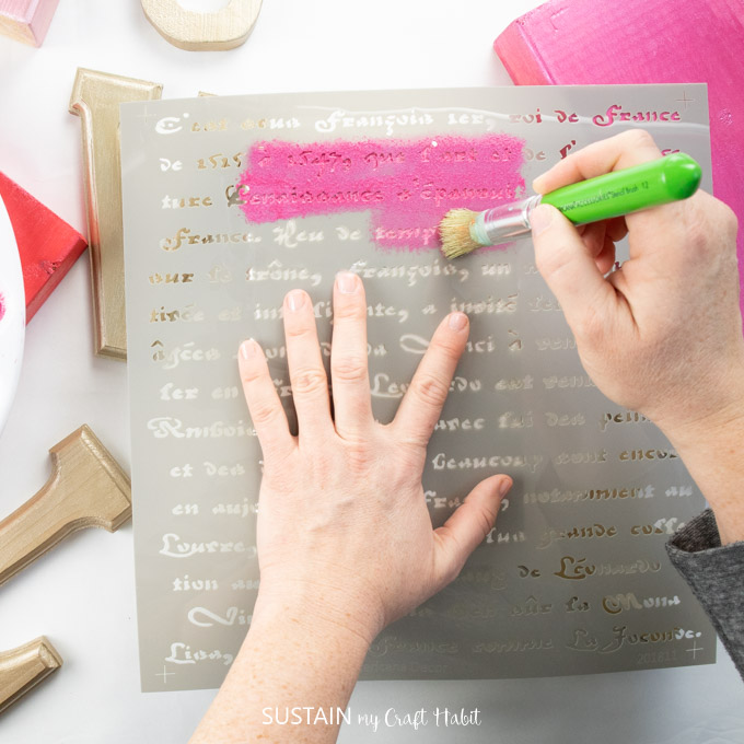 Painting over a french script stencil with pink paint onto a wooden  block.