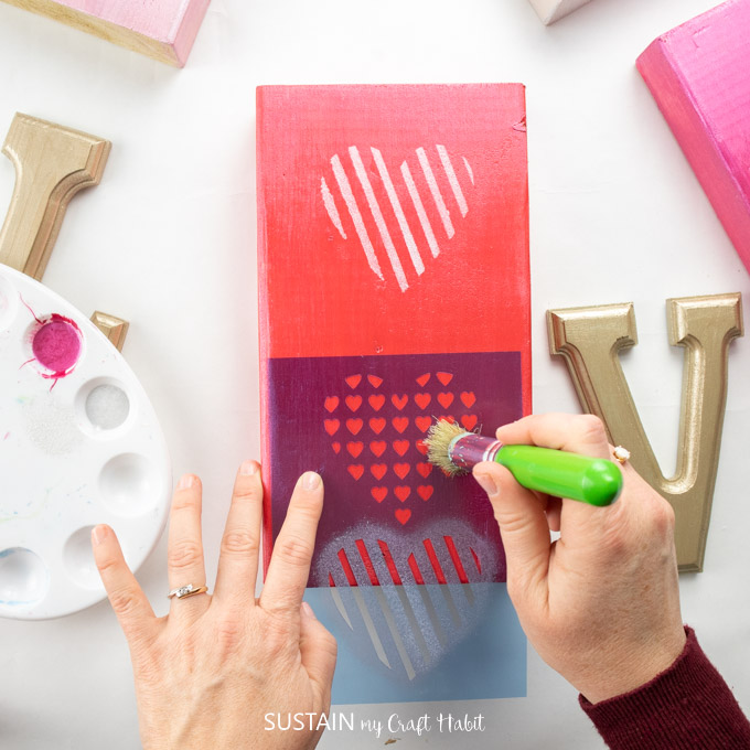 Painting over a heart stencil with silver paint onto a red painted wooden block.