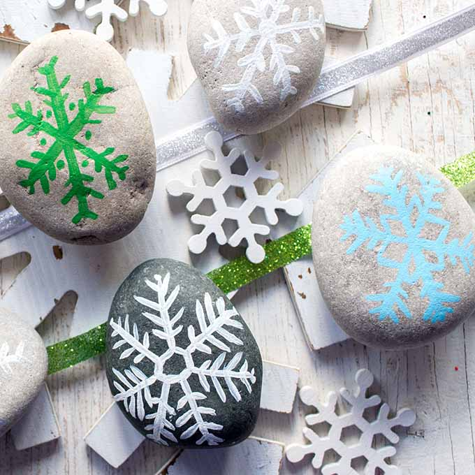 Four rocks painted with snow flake designs. They're placed on top of snowflake decorations and a white table.