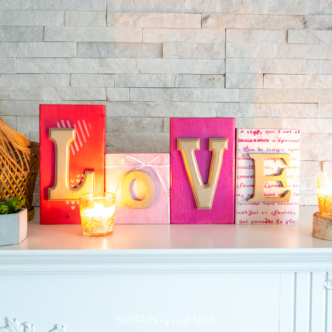 "Colorful wood blocks with gold letters that spell out ""love"". They're sitting on a mantel behind a lit candle."