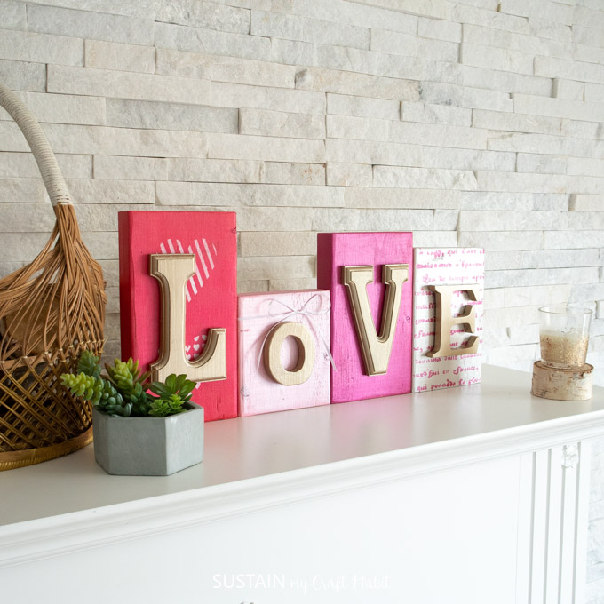 "Colorful wood blocks with gold letters that spell out ""love"". They're sitting on a mantel behind a green succulent plant and candle."