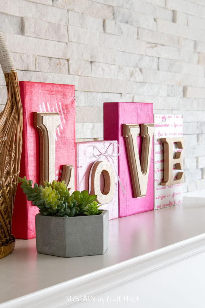 "Colorful wood blocks with gold letters that spell out ""love"". They're sitting on a mantel behind a green succulent plant."