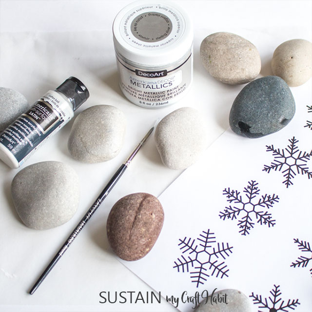 Supplies needed for the rock painting. Includes eight rocks, a paint brush, paint and a snowflake template.