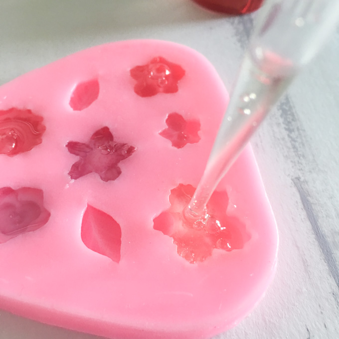 Pouring the resin into a pink silicon mold with flower and leaf molds.