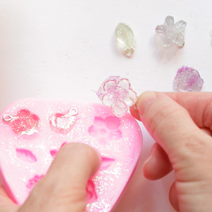 Removing the dried resin flower shape from the pink silicone mold.