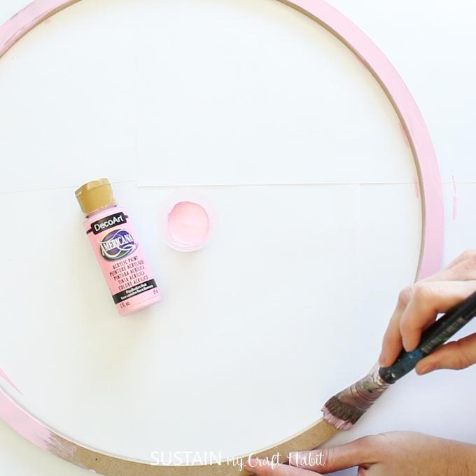 Painting a wood hoop ring pink.