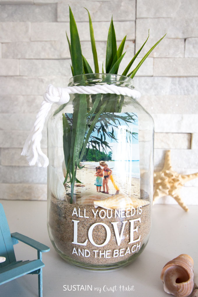 Clear jar filled with sand, sea shells, a picture and long faux greenery. The jar has white rope tied around the rim and is placed near a starfish, sea shell and Adirondack chair.