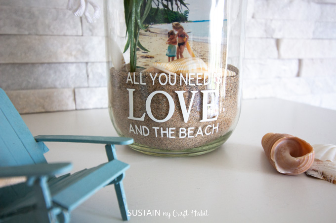 Showing the bottom of the glass jar with the cut out phrase, sand, sea shells and pictures.