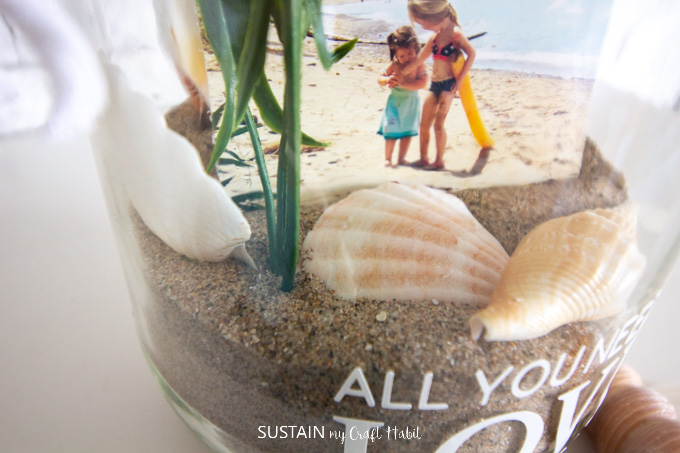 Close up of the sand, sea shells and picture inside the glass jar.