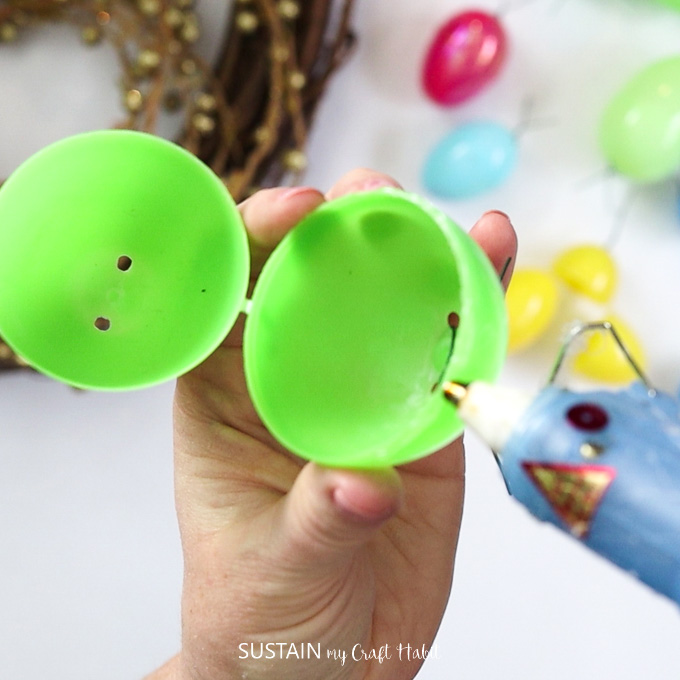 Gluing a green plastic Easter egg.