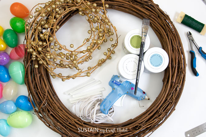 Materials needed to make an Easter wreath. Plastic eggs, gold garland, grapevine wreath, glue gun, paint and paint brush, pliers and floral wire.