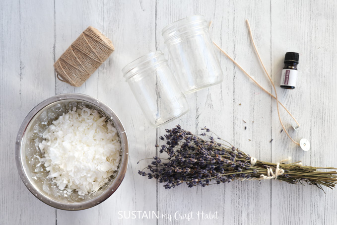 Materials needed to make a dried lavender candle. A bowl with wax, dried lavender, twine, mason jar, wooden skewers and a bottle of essential oil.