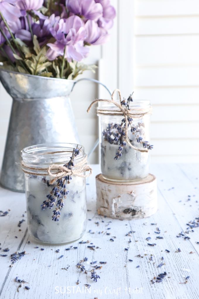 Two mason jar lavender candles wrapped with twine and dried lavender. One candle is placed on a wood slice, both are placed in front of a silver milk jug and scattered lavender buds.