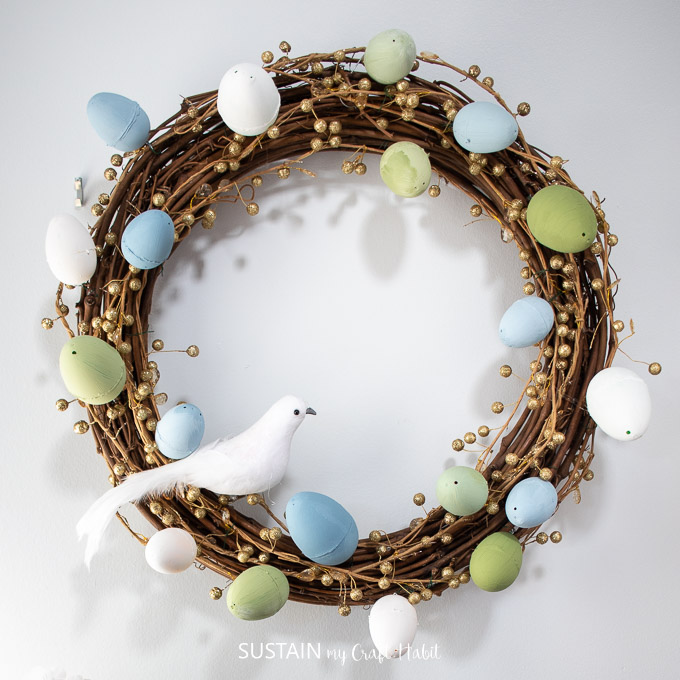 Grapevine wreath decorated with painted Easter eggs, gold garland and a decorative bird
