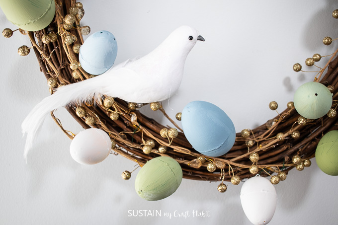 Close up of decorative bird and painted Easter eggs on the grapevine wreath.
