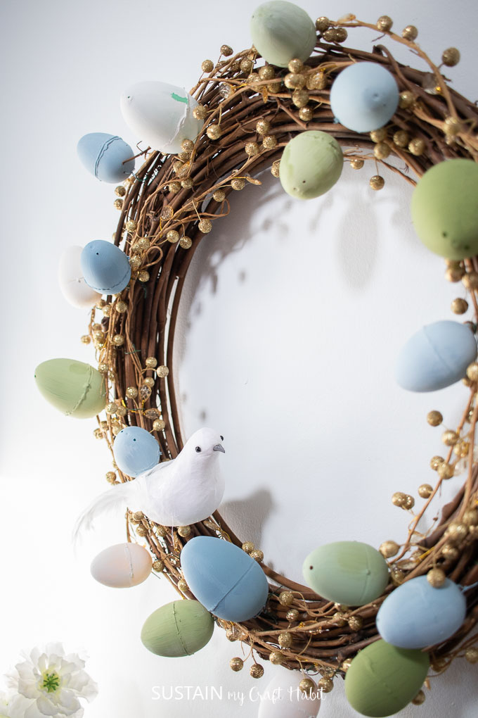 Close up of finished Easter wreath with gold garland, painted Easter eggs and a decorative bird.