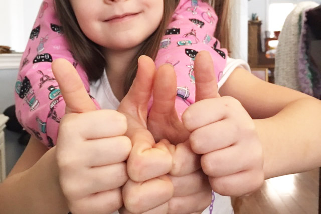 Close up image of two girls holding their thumbs up.