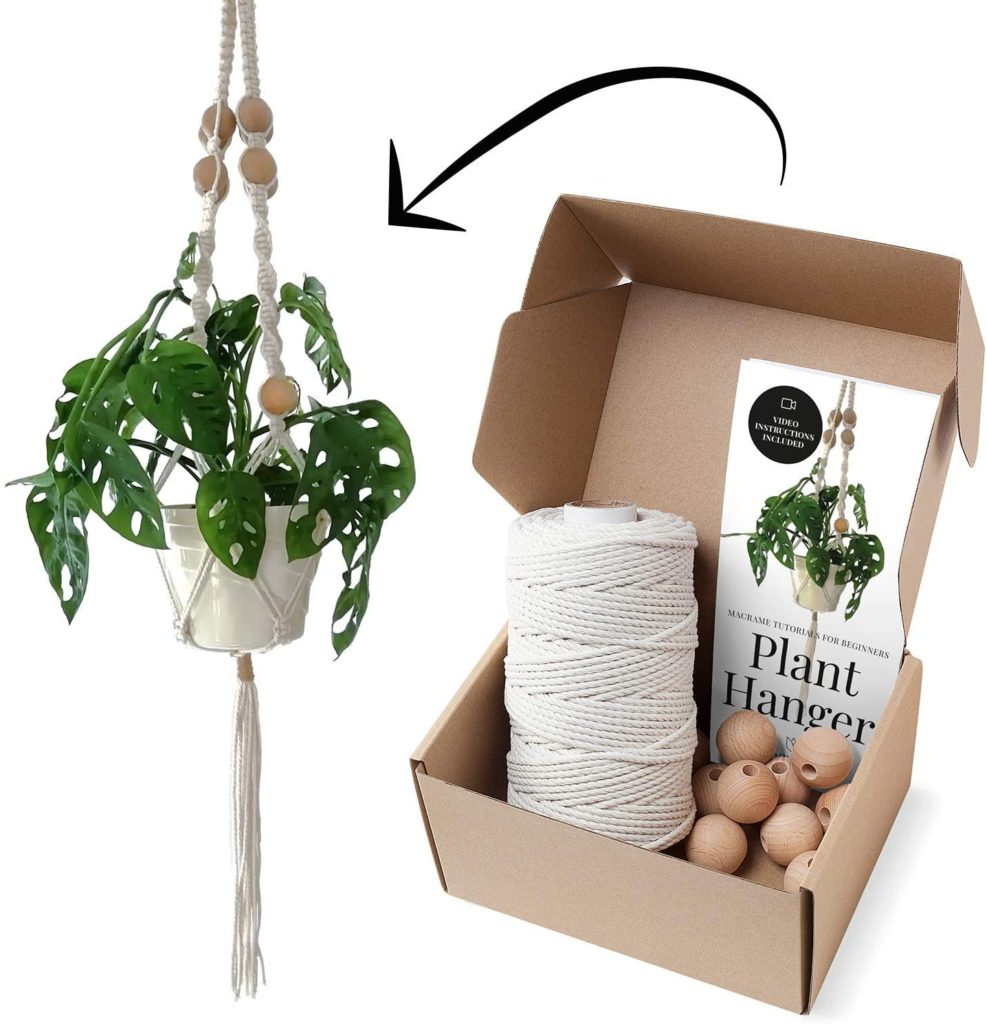 A potted monstera plant in a completed macrame plant hanger. A cardboard box with the materials and instructions to make the planter.