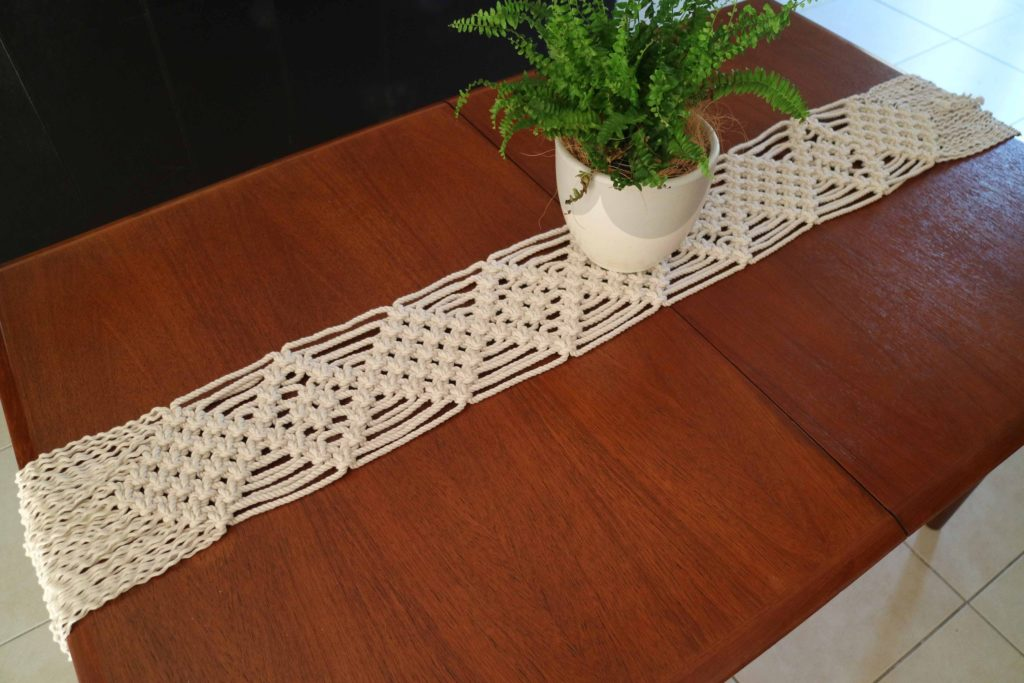 A completed macrame table runner on a cherry colored wood table surface.