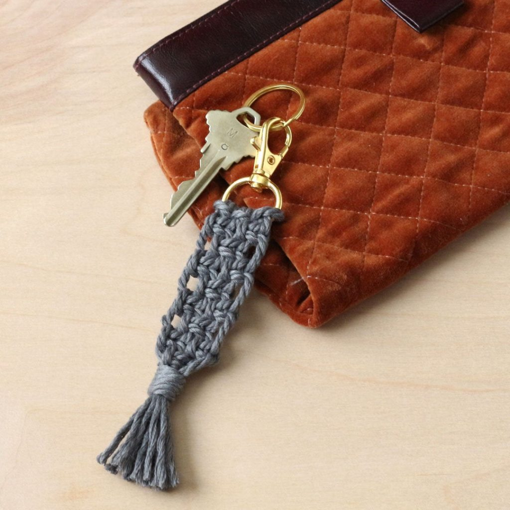 Close up image of a gray macrame keychain connected to a gold clasp resting against a rust colored purse.