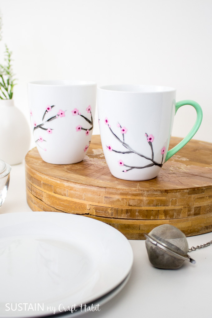 Two white mugs painted with cherry blossoms and green handles. The mugs are sitting on a wood tray beside white plates, a vase and tea infuser.