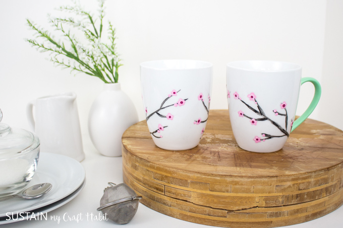 Two mugs painted with cherry blossoms and green handles. The mugs are sitting on a wood tray beside white plates, a vase and tea infuser.