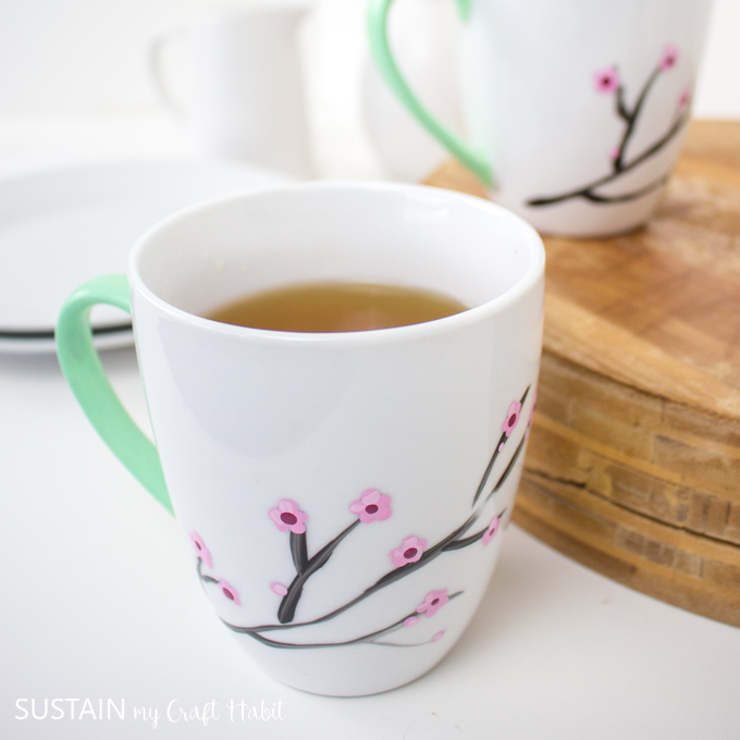 Close up of a white mug with a green painted handle and painted cherry blossoms on the front.