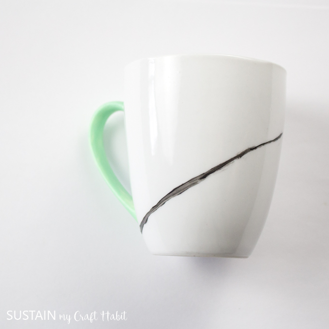 Adding a diagonal line with black paint on a white mug.