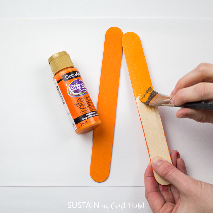 Painting a wooden popsicle stick in DecoArt orange color.