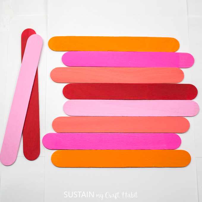 Painted popsicle sticks faced down and assembled horizontally with 2 sticks off to the side.