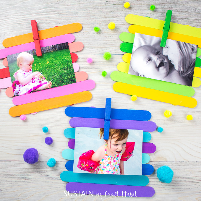 Colorfully painted Popsicle sticks made into photo frames holding a picture in each frame by a painted clothes pin. The frames are surrounded by pompoms.