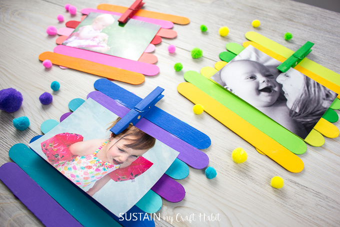 Colorfully painted Popsicle sticks made into photo frames holding a picture in each frame by a painted clothes pin. The frames are surrounded by pompoms and buttons.