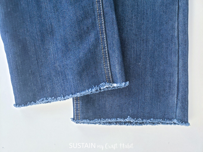 A pair of demin pants with a frayed edge hem.