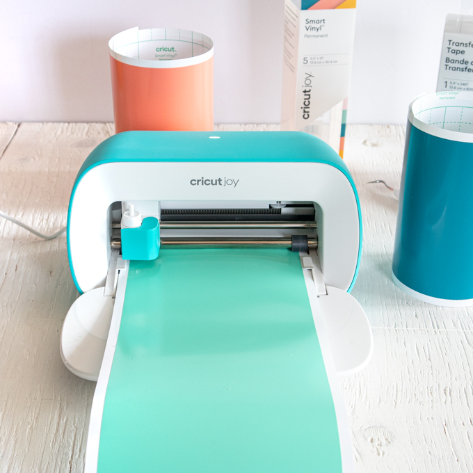 Inserting the green vinyl to the Cricut Joy