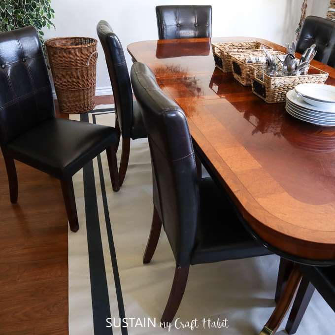 DIY painted canvas rug beneath a large wooden dining table