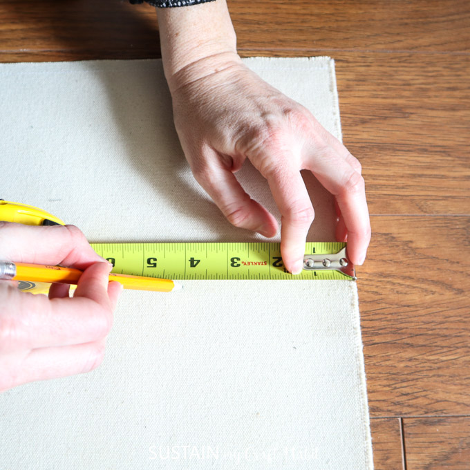 measuring the canvas from the edge to place the painter's tape for painting