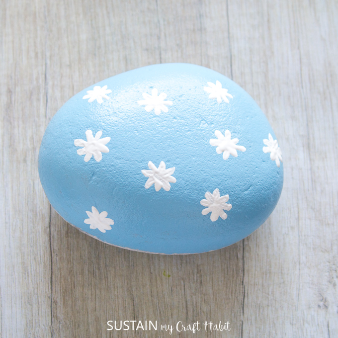 White painted flowers on blue painted rock