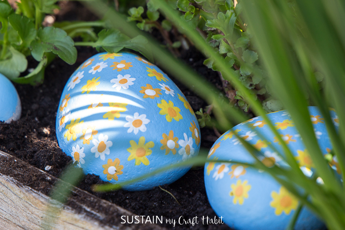 Close up of flower painted rocks sitting in a garden bed.