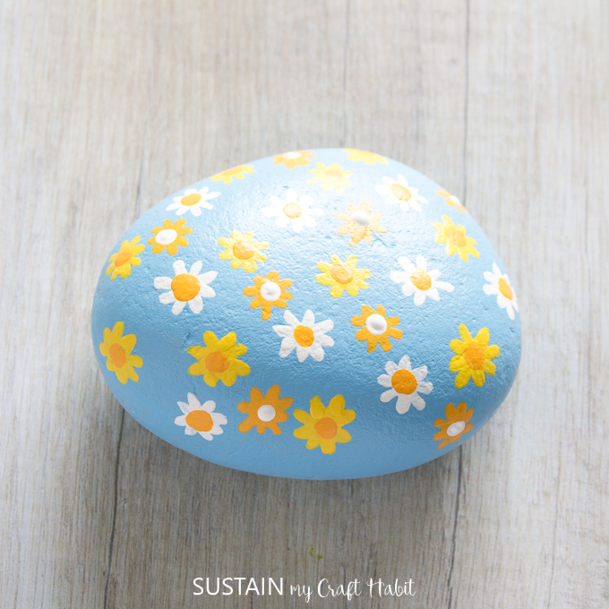 Finished daisy flowers painted on a blue rock.