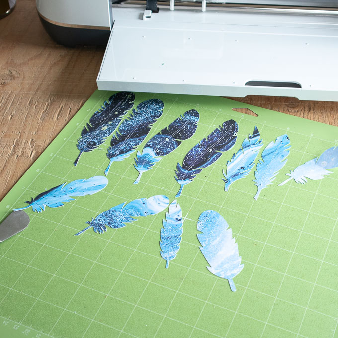 Blue paper feathers on a green grip mat.