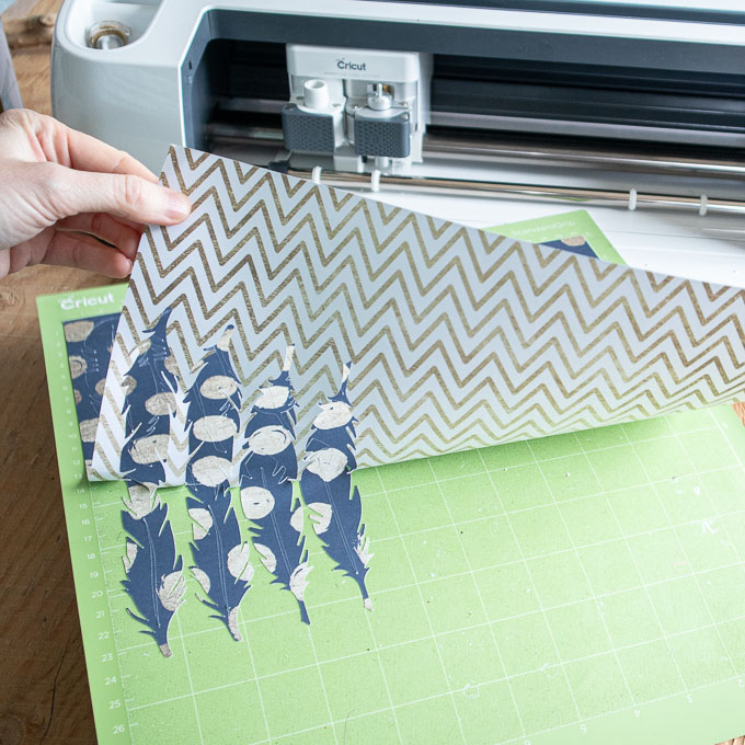 Removing the cut polka dot paper feathers from the Cricut machine.